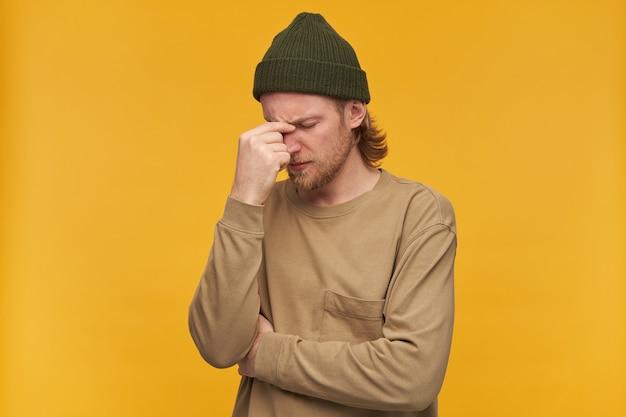 Homme stressé, gars fatigué aux cheveux blonds, barbe et moustache. porter un bonnet vert et un pull beige. toucher le pont du nez dans la douleur. se concentrer. stand isolé sur mur jaune