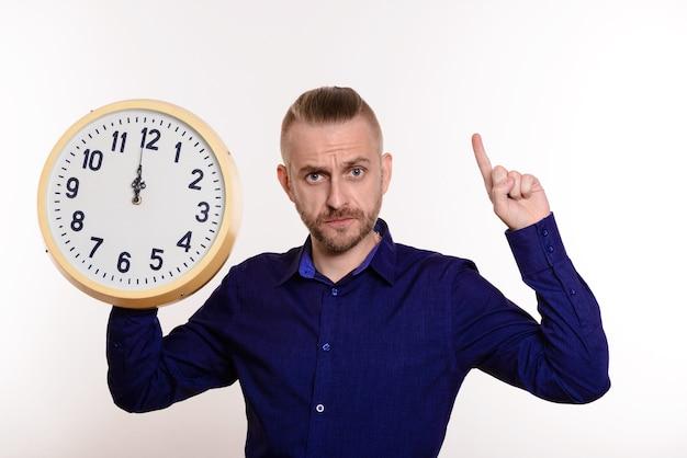 Homme strict tenant une grande horloge murale et pointe un doigt sur l'espace vide sur blanc