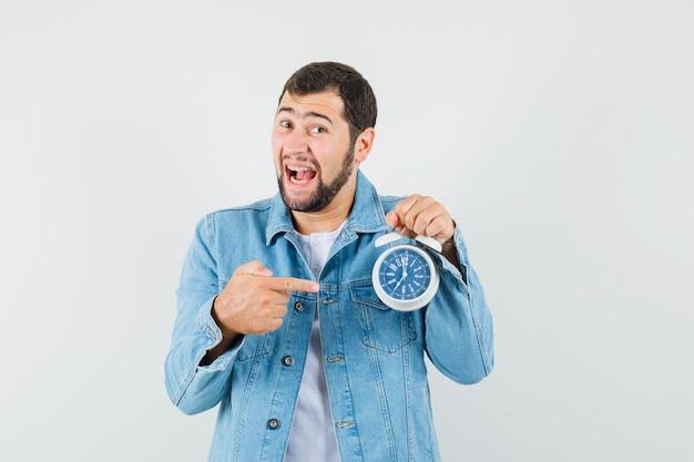 Homme de style rétro en veste, t-shirt pointant sur l'horloge et regardant heureux, vue de face.