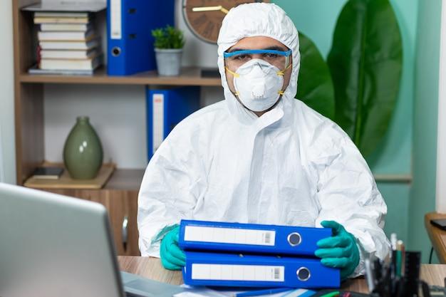 Homme avec une suite blanche spéciale tenant des documents au bureau