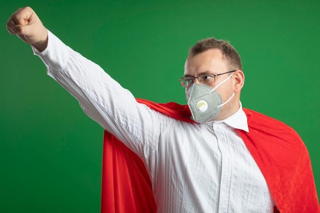 Homme de super-héros adultes confiant en cape rouge portant des lunettes et un masque de protection à côté levant le poing isolé sur mur vert