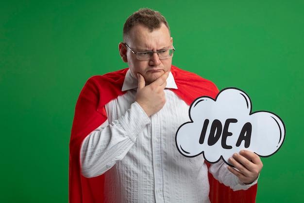 Homme de super-héros adultes confus en cape rouge portant des lunettes tenant et regardant la bulle d'idée touchant le menton isolé sur le mur vert