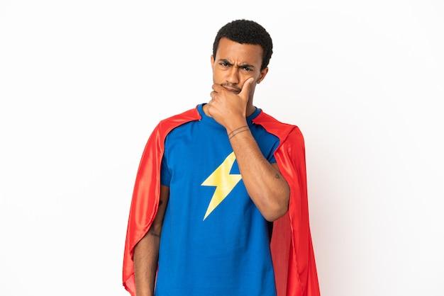Homme super-héros afro-américain sur fond blanc isolé ayant des doutes et avec une expression de visage confuse