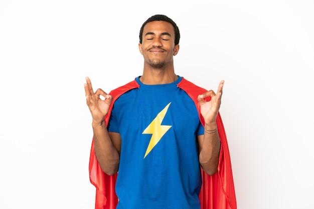 Homme super-héros afro-américain sur fond blanc isolé dans une pose zen