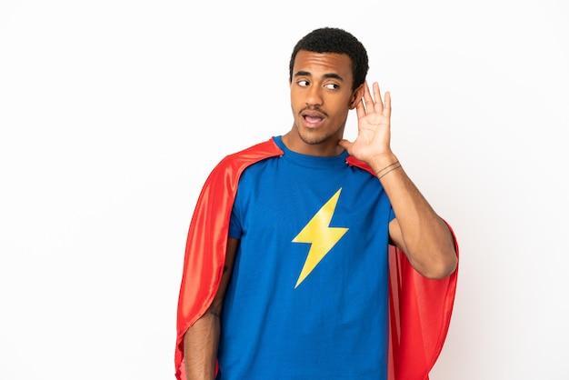 Homme super-héros afro-américain sur fond blanc isolé écoutant quelque chose en mettant la main sur l'oreille