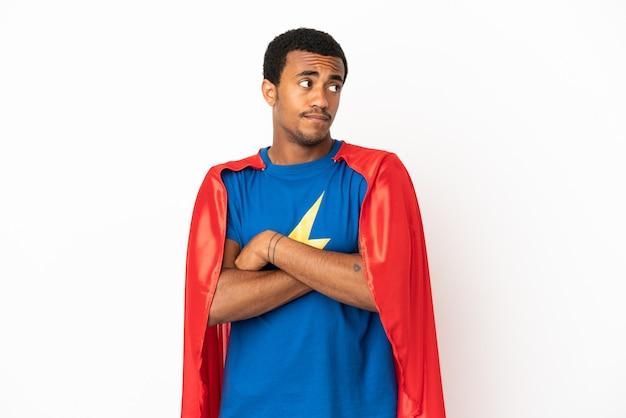Homme super-héros afro-américain sur fond blanc isolé faisant un geste de doute tout en soulevant les épaules
