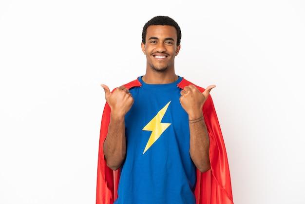 Homme super-héros afro-américain sur fond blanc isolé avec un geste de pouce levé et souriant