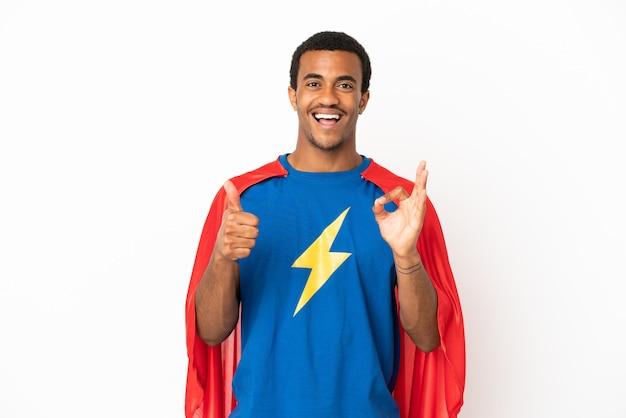 Homme super-héros afro-américain sur fond blanc isolé montrant signe ok et geste du pouce vers le haut