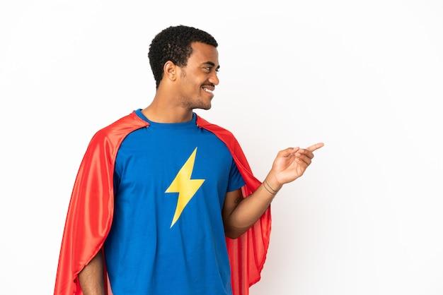 Homme super-héros afro-américain sur fond blanc isolé, pointant le doigt sur le côté et présentant un produit