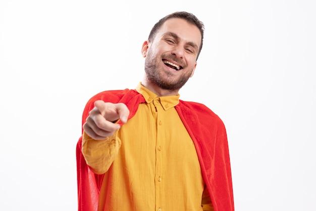 Un homme de super-héros caucasien joyeux avec une cape rouge regarde et pointe vers la caméra
