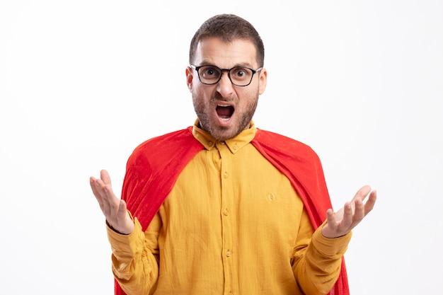 Homme de super-héros en colère dans des lunettes optiques avec manteau rouge se tient la main ouverte isolé sur un mur blanc