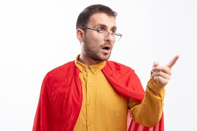 Homme de super-héros confiant dans des lunettes optiques avec cape rouge regarde et pointe sur le côté isolé sur mur blanc