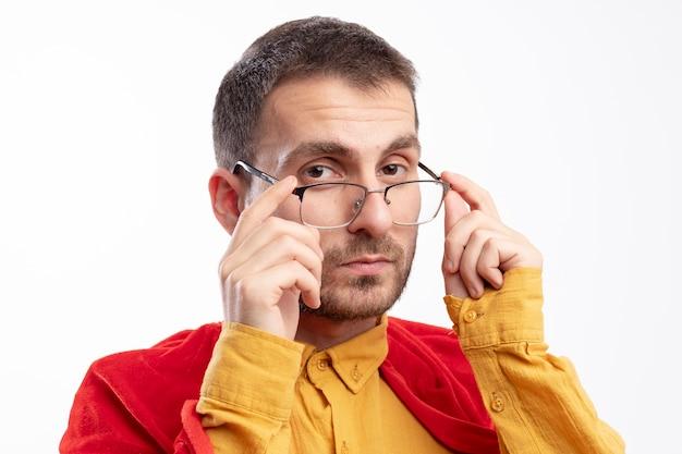 Homme de super-héros confiant avec manteau rouge détient des lunettes optiques et regarde à l'avant isolé sur un mur blanc