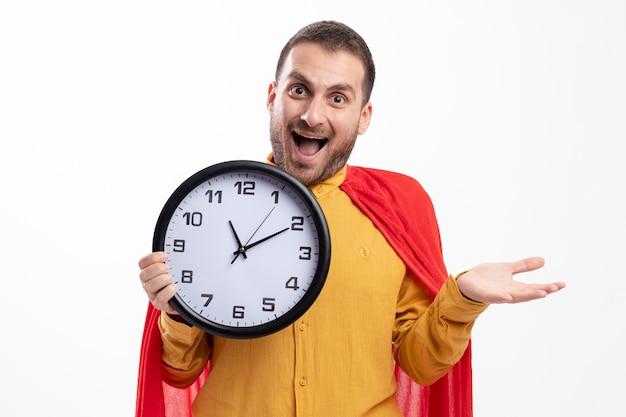 Homme de super-héros excité avec manteau rouge détient horloge isolé sur mur blanc