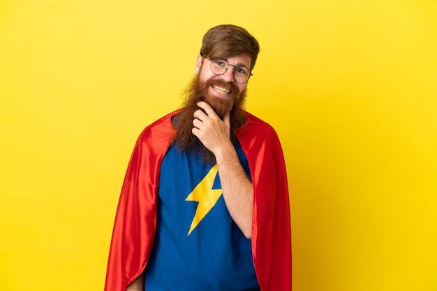 Homme super héros rousse isolé sur fond jaune avec des lunettes et souriant