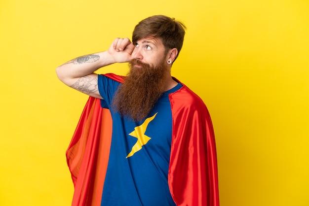 Homme super héros roux isolé sur fond jaune ayant des doutes et avec une expression de visage confuse