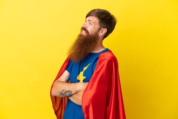 Homme super héros roux isolé sur fond jaune avec les bras croisés et heureux