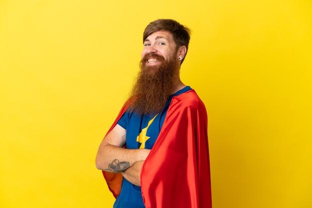 Homme super héros roux isolé sur fond jaune avec les bras croisés et impatient