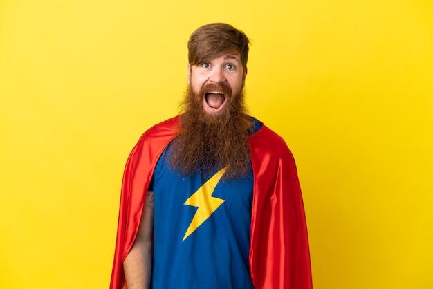 Homme super héros roux isolé sur fond jaune avec une expression faciale surprise