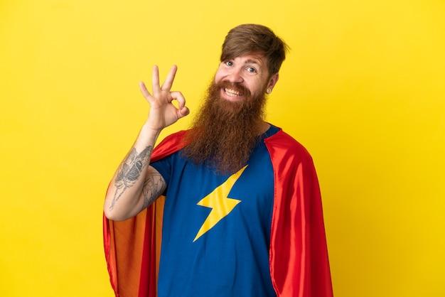 Homme super héros roux isolé sur fond jaune montrant un signe ok avec les doigts