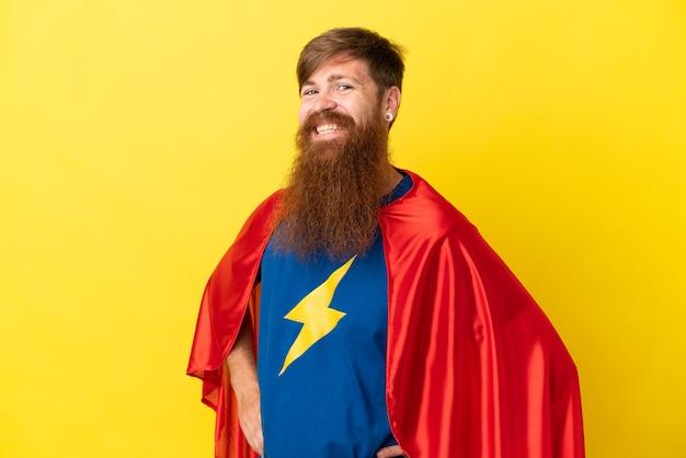 Homme super héros roux isolé sur fond jaune posant avec les bras à la hanche et souriant