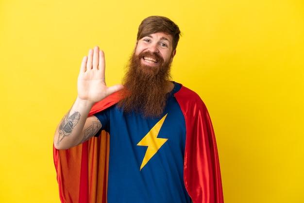 Homme super héros roux isolé sur fond jaune saluant avec la main avec une expression heureuse
