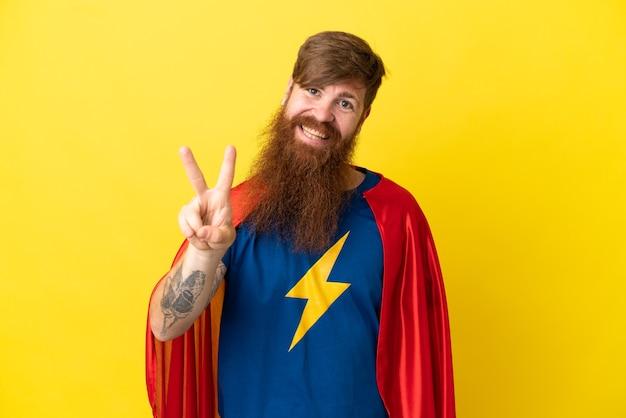 Homme de super héros roux isolé sur fond jaune souriant et montrant le signe de la victoire