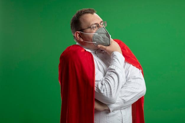 Homme de super-héros slave adulte réfléchi en cape rouge portant des lunettes et un masque de protection à la recherche de menton touchant droit isolé sur un mur vert avec espace de copie