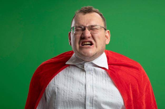 Homme de super-héros slaves adultes agacé en cape rouge portant des lunettes avec les yeux fermés isolé sur mur vert