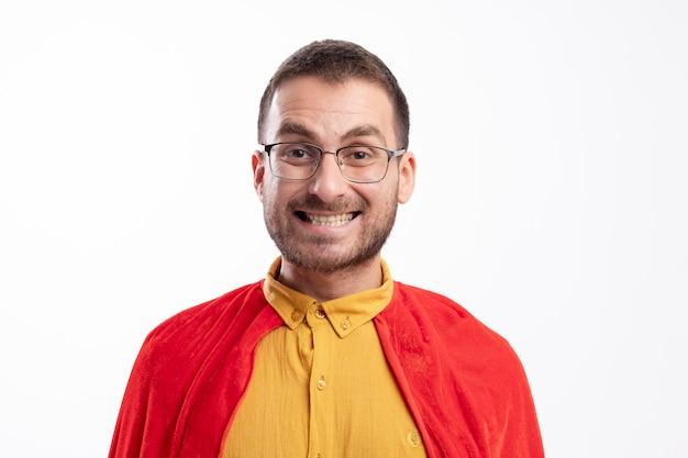 Homme de super-héros souriant à lunettes optiques avec manteau rouge isolé sur mur blanc