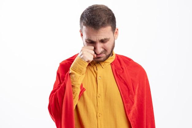 Homme de super-héros triste avec manteau rouge tient le poing sous la paupière isolé sur mur blanc