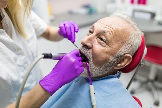 Homme supérieur ayant un traitement dentaire au cabinet du dentiste.