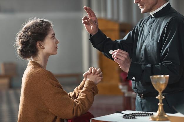 Homme supérieur bénissant la femme pendant qu'elle priait dans l'église