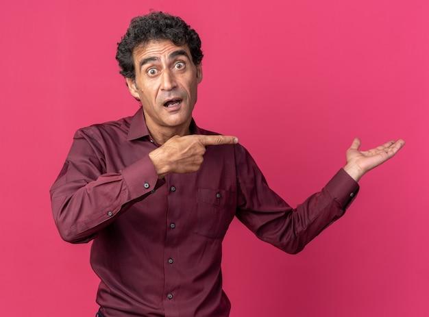 Homme supérieur en chemise violette regardant la caméra surpris