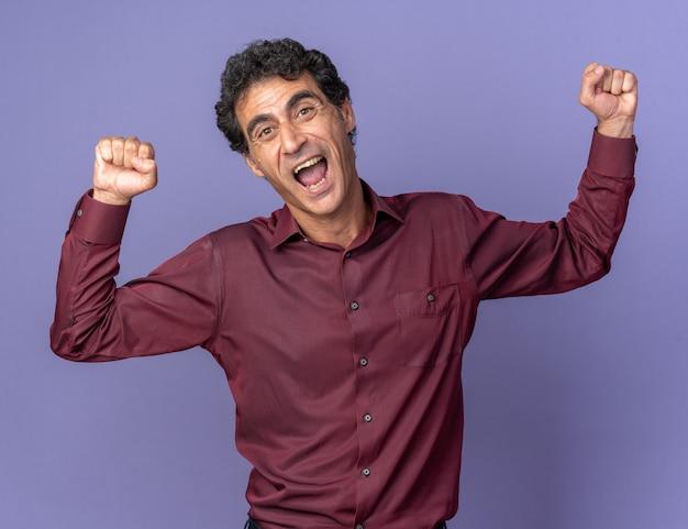 Homme supérieur en chemise violette serrant les poings heureux et excité se réjouissant debout sur fond bleu