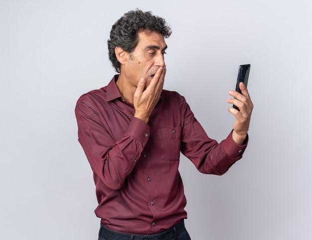 Homme supérieur en chemise violette tenant un smartphone en le regardant étonné et choqué debout sur blanc
