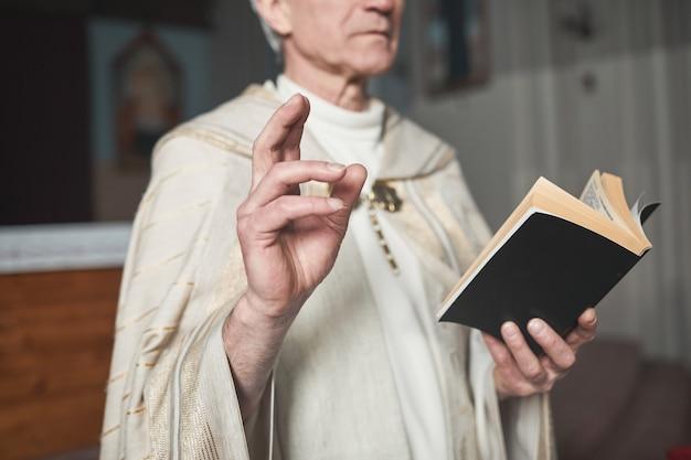 Homme supérieur en costume lisant des prières de la bible en se tenant debout dans l'église