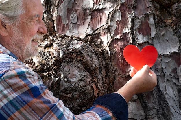 L'homme supérieur dans les bois met une forme de coeur sur le tronc d'arbre concept de jour de la terre. ensemble, sauvez la planète de la déforestation