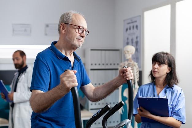 Homme supérieur faisant l'exercice physique pour la récupération orthopédique