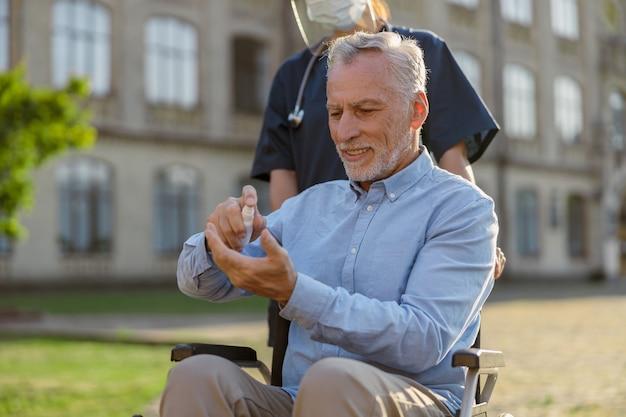 Homme supérieur en fauteuil roulant se nettoyant les mains avec un désinfectant antibactérien comme mesure d'hygiène pour