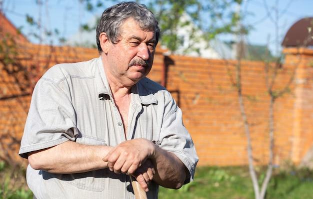 Homme supérieur jardinant, travaillant dans le jardin, s'appuyant sur le manche d'une pelle et se reposant après avoir creusé les lits dans le jardin