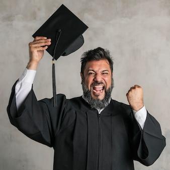 Homme supérieur joyeux dans une robe de graduation