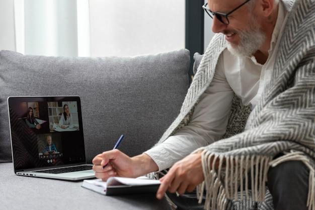 Homme supérieur à la maison étudiant sur ordinateur portable et prenant des notes