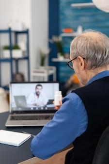 Homme supérieur montrant une bouteille de pilules au médecin tout en utilisant un ordinateur portable pour la télémédecine
