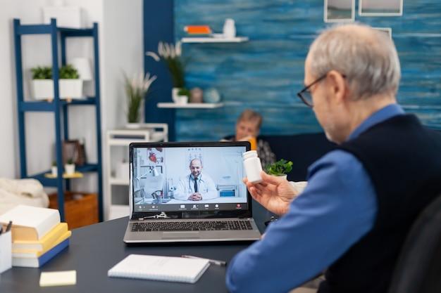 Homme supérieur montrant la bouteille de pilules de docteur à la webcam pendant l'appel vidéo