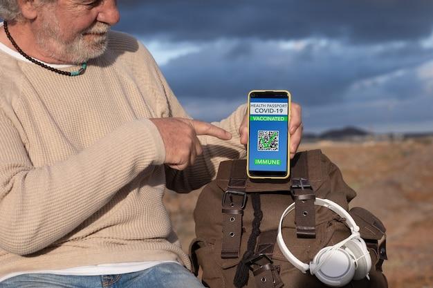 Homme supérieur montrant le laissez-passer vert pour voyager sur l'application mobile. voyageur heureux avec sac à dos