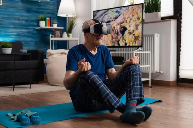 Homme supérieur portant un casque de réalité virtuelle pratiquant l'exercice de méditation assis sur un tapis de yoga