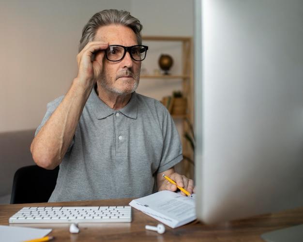Homme supérieur prenant une classe en ligne sur son ordinateur