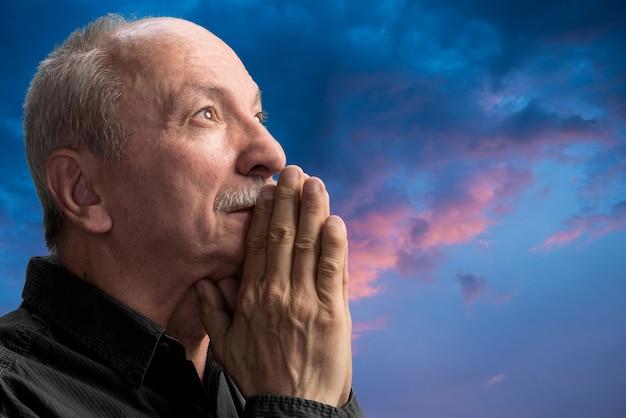 Homme supérieur priant contre le ciel nuageux bleu