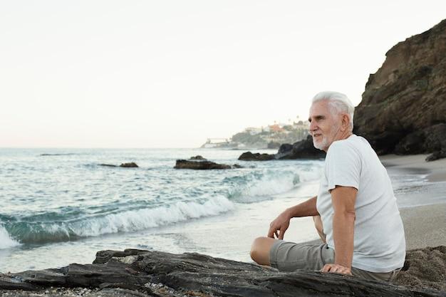 Homme supérieur se reposant à la plage et admirant l'océan
